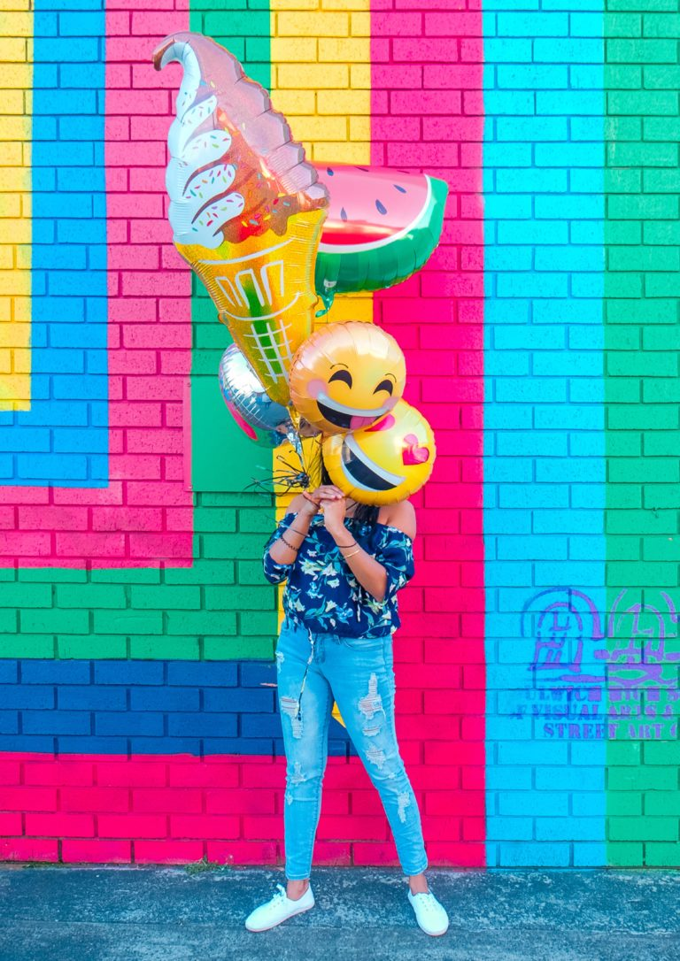 A woman hiding behind balloons with bright colors behind her